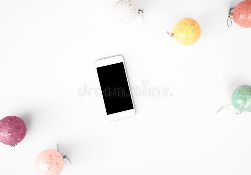 Bewegliche Anzeige des intelligenten Telefons auf Tabelle Weihnachtszusammensetzungshintergrund tapezieren Sie, Dekorationsbälle, stockfotografie
