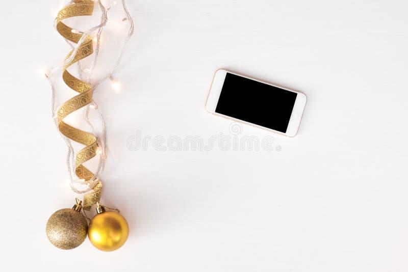 Bewegliche Anzeige des intelligenten Telefons auf Tabelle Weihnachtszusammensetzungshintergrund tapezieren Sie, Kiefernkegel, Dek lizenzfreie stockfotos