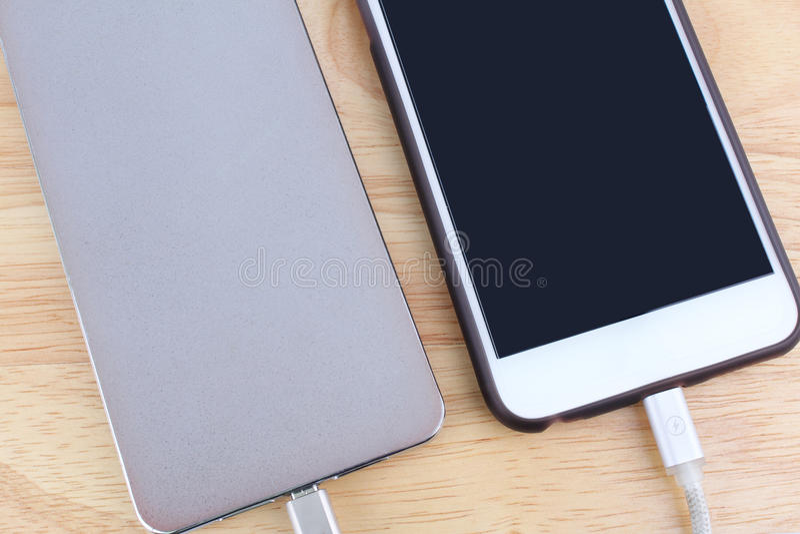 Bewegliche Aufladung Smartphones mit der Energiebank lokalisiert auf weißem Ba lizenzfreie stockfotos