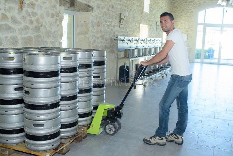 Bewegliche Fässer der Arbeitskraft mit Gabelhubwagen stockfotos
