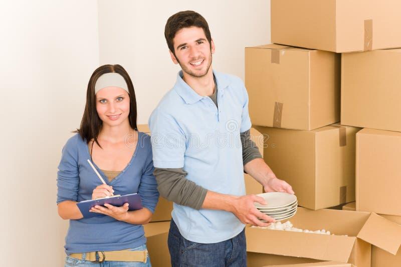 Bewegliche junge glückliche Hauptpaare, die Kästen entpacken lizenzfreie stockfotos