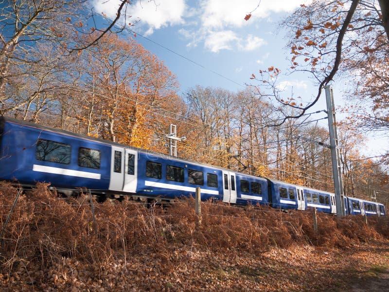 Bewegliche Zugbewegung verwischte blaue Bahnen außerhalb des Herbstlandes stockbild