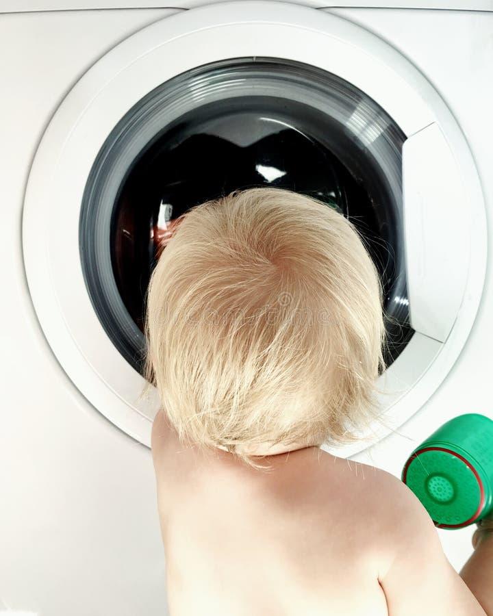 Bewegliches Foto des blonden Kind-hindhead vor Waschmaschine stockfotos