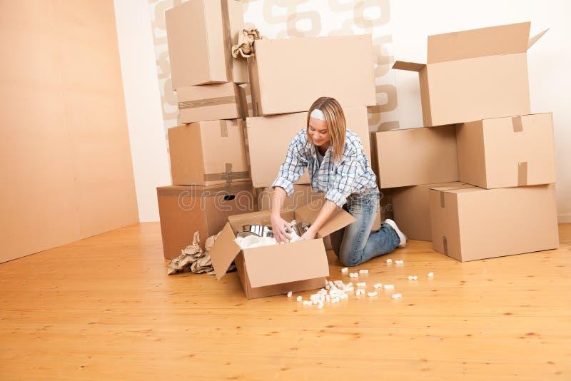 Bewegliches Haus: Glückliche Frau, die Kasten entpackt stockfotografie