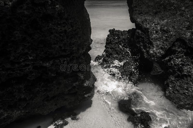 Bewegung des Wassers wird mittels des Blinkens eingefroren Haarscharfes Meerwasserschlagen gegen den Roc lizenzfreie stockfotos