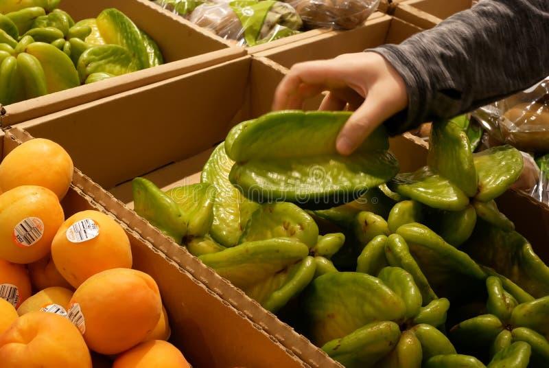 Bewegung von Frau ` s Handsammeln starfruit innerhalb des Superstore lizenzfreies stockfoto