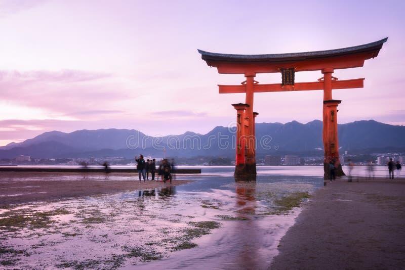 Bewegung von Leuten und von Gezeiten am berühmten Torii-Tor bei Sonnenuntergang - Miyajima, Japan stockfotografie