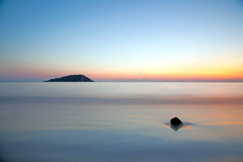 Bewegungsunschärfe des Meeres unter klarem Dämmerungssonnenunterganghimmel lizenzfreies stockfoto