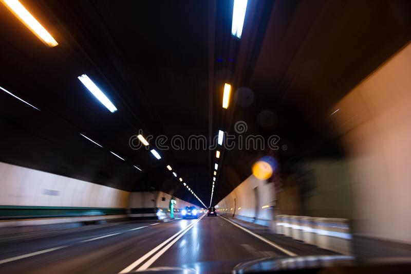 Bewegungsunschärfe, die Auto mit Geschwindigkeit durch einen Tunnel nachts fährt stockbilder