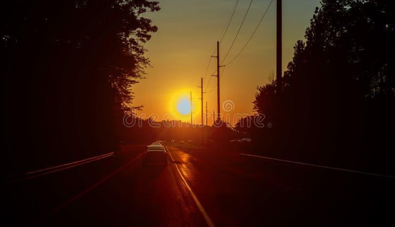 Bewegungsunschärfelandstraßenverkehr in Sonnenuntergang Straßenlauf durch Wald lizenzfreie stockfotos