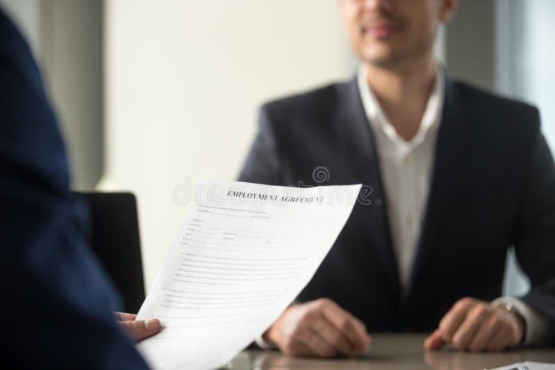 Bewerber, der die Betriebsvereinbarung, Arbeit ter betrachtend hält lizenzfreies stockbild