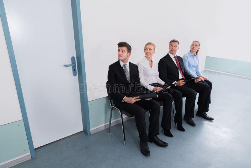 Bewerber, die auf Stuhl im Büro sitzen lizenzfreie stockfotos