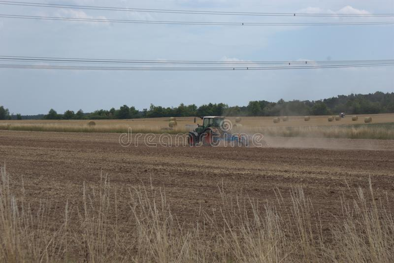 Bewerkend harrowing tractor een droog gebied, na een de zomeroogst, en het werpen op heel wat stof van de droge landbouwgrond royalty-vrije stock afbeelding