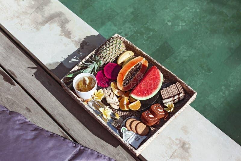 Bewerkte lade met fruitplaat per hotelpool op Bali villa stock foto's