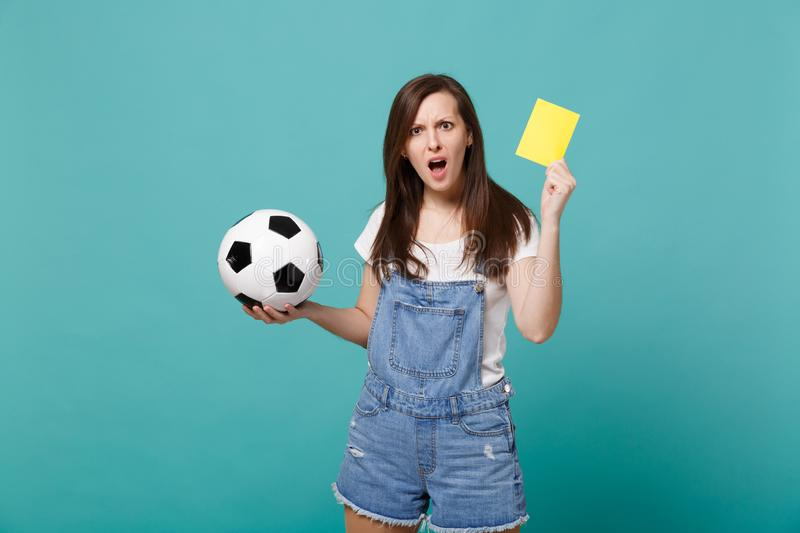 Bewildered girl football fan support team with soccer ball, yellow card, swearing propose player retire from field. Isolated on blue turquoise background stock photos