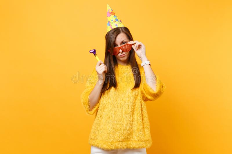 Bewildered puzzled woman in birthday hat holding orange funny glasses with playing pipe standing celebrating isolated on. Yellow background. People sincere stock photos