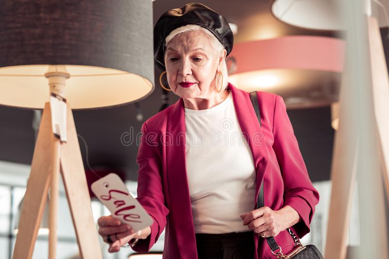 Bewitching elegant senior lady looking at sale sign in hand. Sale sign. Bewitching elegant senior lady in leather beret, pink blazer and golden accessories royalty free stock photos