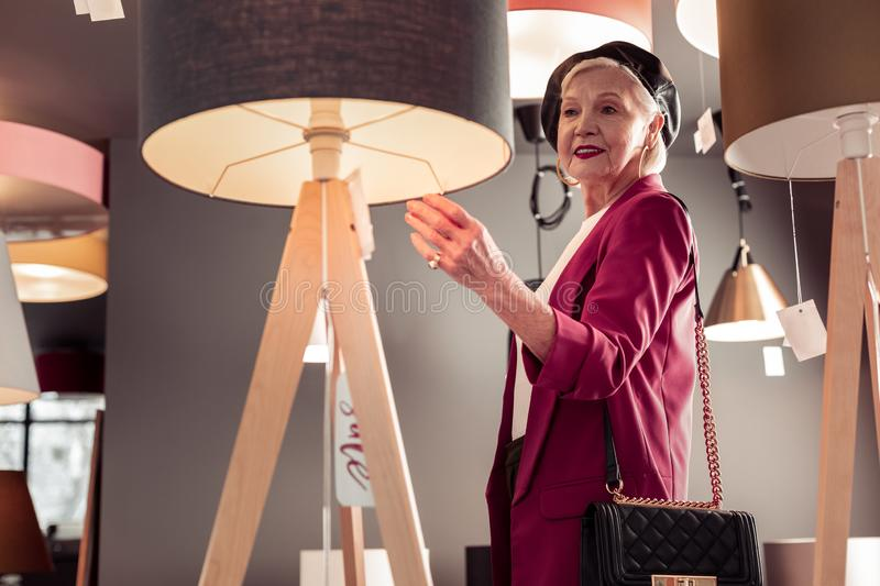 Bewitching stylish elderly female designer choosing new interior lamp. Buying new torcher. Bewitching stylish elderly female grey-haired designer choosing a new royalty free stock images
