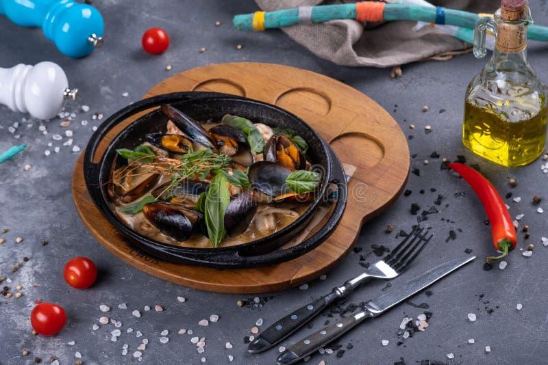 Bewogen gebraden zeeschelpen met oestersaus en groene basilicumbladeren, een heerlijke zeevruchtenschotel, op pan stock foto's