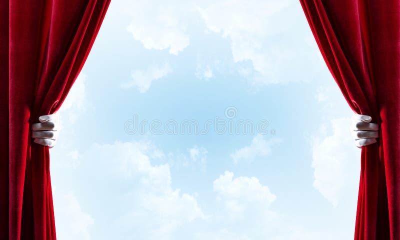 Bewolkt landschap achter rode gordijn en handholding het stock foto's