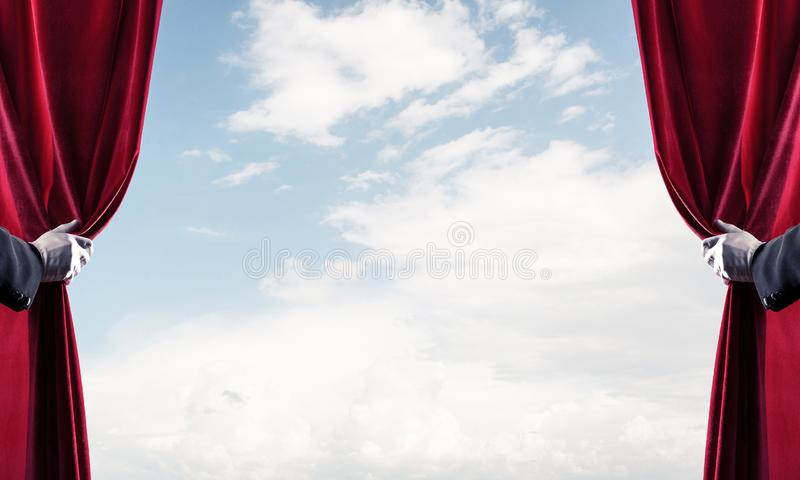 Bewolkt landschap achter rode gordijn en handholding het stock foto