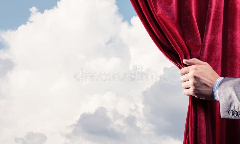 Bewolkt landschap achter rode gordijn en handholding het royalty-vrije stock foto's
