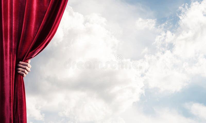 Bewolkt landschap achter rode gordijn en handholding het royalty-vrije stock fotografie