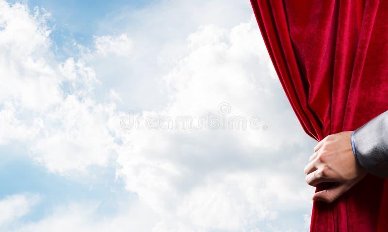 Bewolkt landschap achter rode gordijn en handholding het royalty-vrije stock afbeelding