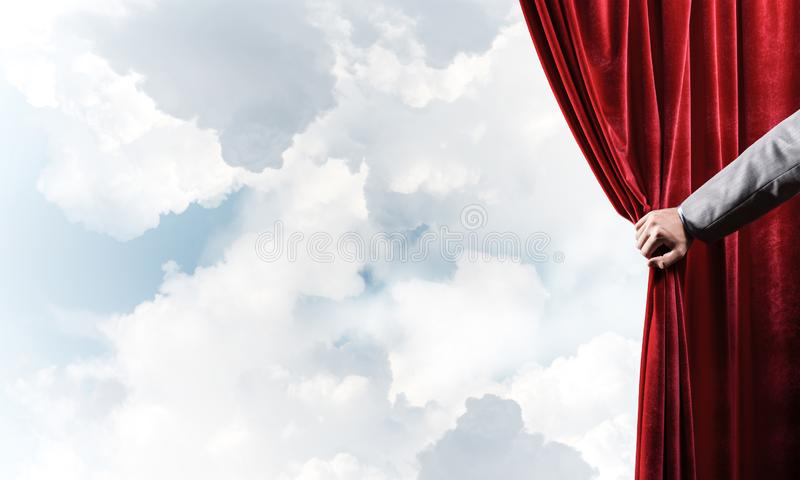Bewolkt landschap achter rode gordijn en handholding het royalty-vrije stock foto