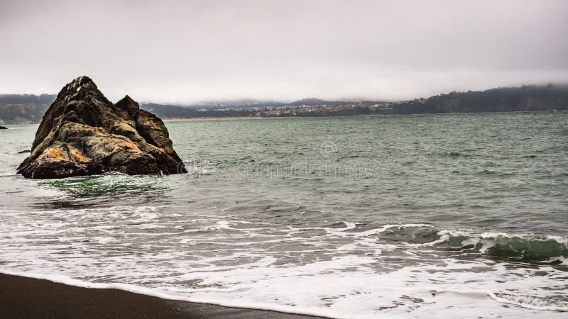 Bewolkte en mistige dag op de oever van de Vreedzame Oceaan in Marin Headlands; woonbuurt in zichtbaar San Francisco stock afbeeldingen