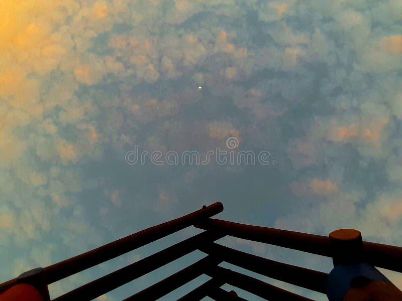 Bewolkte hemel en houten dak stock afbeelding