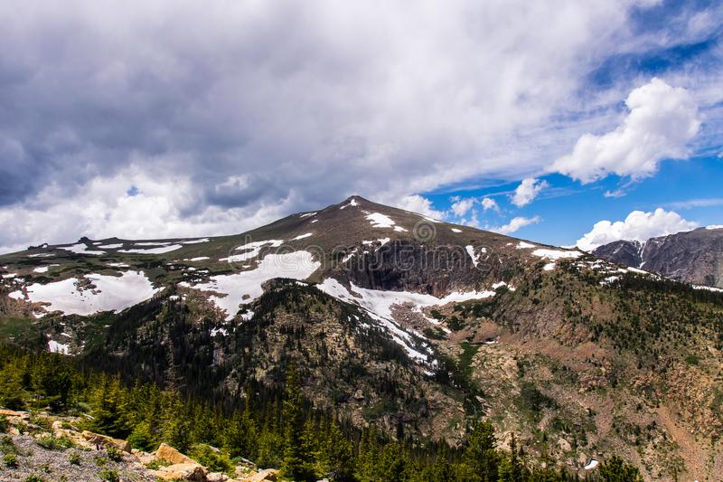 Bewolkte hemel en sneeuwpieken van Rocky Mountains stock foto's