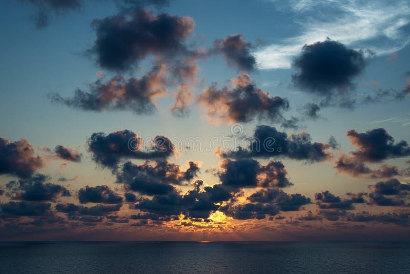 Bewolkte hemel met zonnestraal op de oceaan in zonsondergangtijd royalty-vrije stock foto