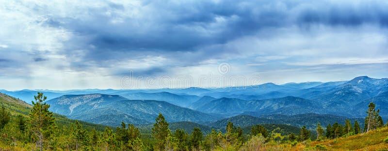 Bewolkte hemel over blauwe bergketen stock foto