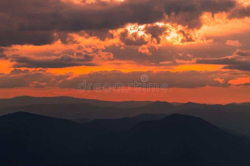 Bewolkte kleurrijke zonsondergang meer dan de hoogten bergen royalty-vrije stock fotografie