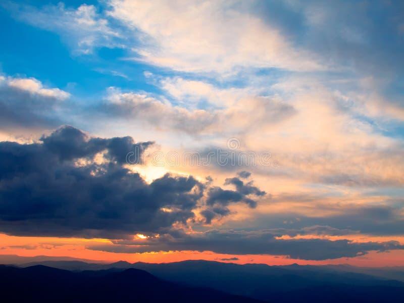 Bewolkte kleurrijke zonsondergang meer dan de hoogten bergen stock foto's