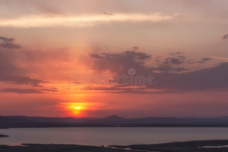 Bewolkte kleurrijke zonsondergang over de heuvels en het meer, Enisala stock afbeelding