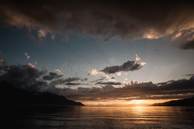 Bewolkte oranje zonsondergang over meer royalty-vrije stock afbeelding