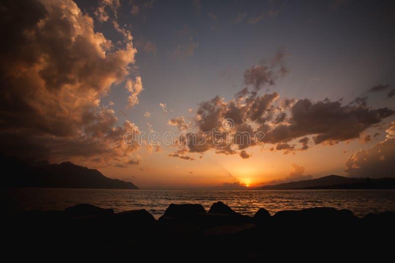 Bewolkte oranje zonsondergang over meer royalty-vrije stock afbeeldingen