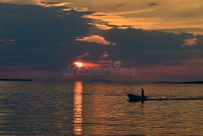 Bewolkte zonsondergang boven de baai van Vrsi Mulo in Kroatië met silhouet van visser een zijn boot die naar huis varen royalty-vrije stock fotografie