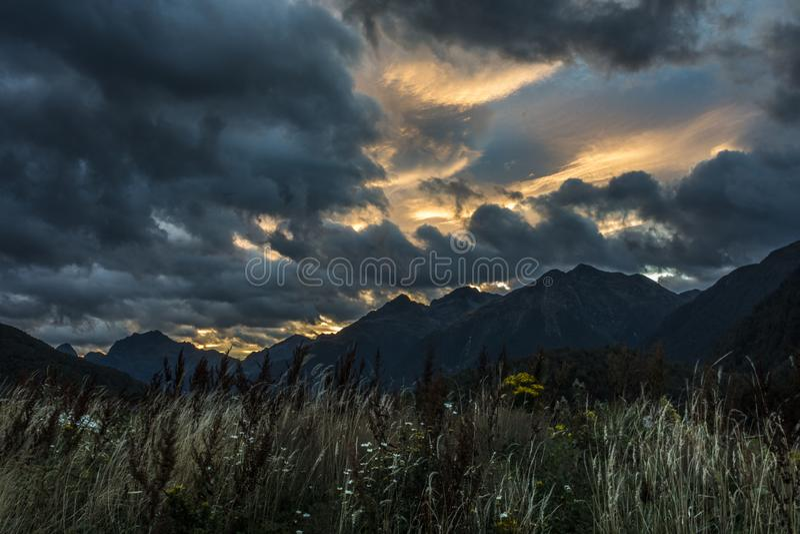 Bewolkte zonsondergang in de bergen royalty-vrije stock foto