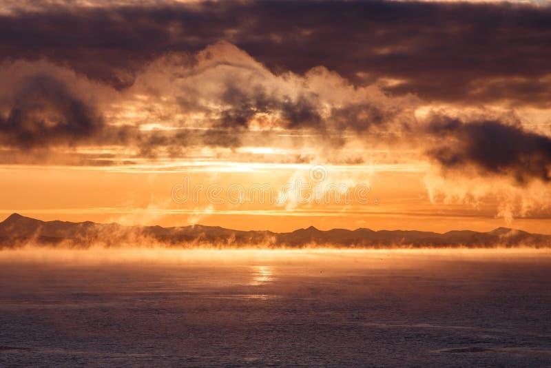 Bewolkte zonsopgang over bergachtige zeekust royalty-vrije stock afbeeldingen