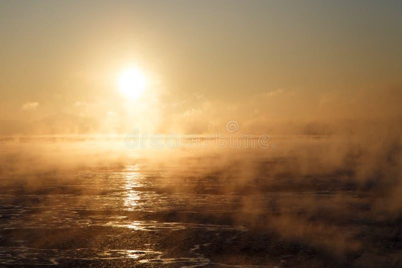 Bewolkte zonsopgang over bergachtige zeekust stock afbeelding