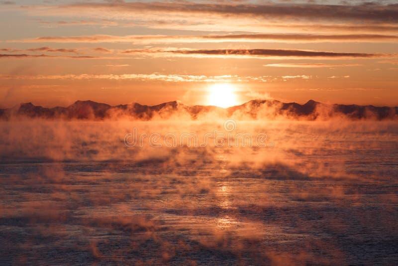 Bewolkte zonsopgang over bergachtige zeekust stock afbeeldingen
