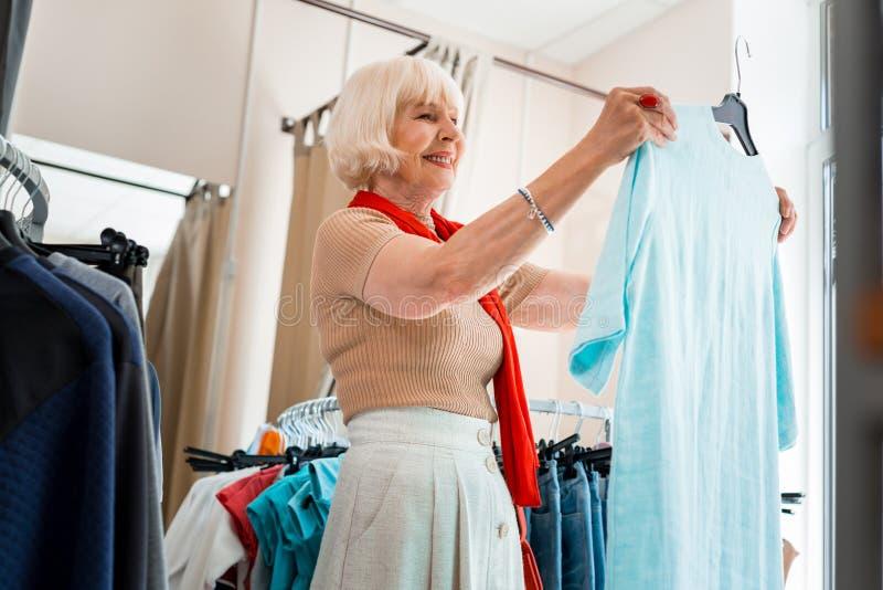 Bewundern Sommerkleid der erfreuten älteren Frau im Bekleidungsgeschäft stockbilder