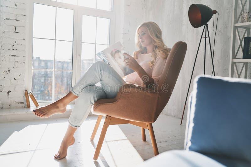 Bewusst Nachrichten der neuesten Mode Schöne junge Frau, die ein MA liest stockfotos