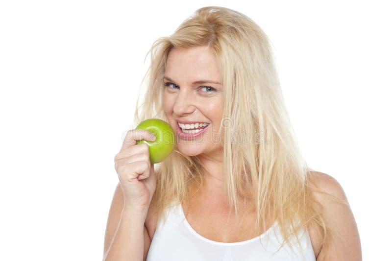 Bewusste Frau der Gesundheit ungefähr, zum des Bisses vom grünen Apfel zu nehmen stockfotos