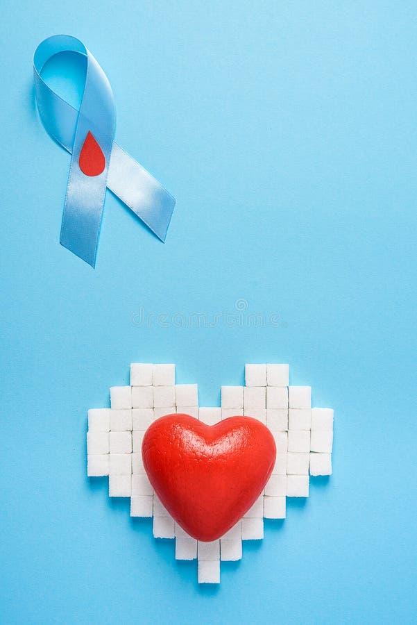 Bewusstsein des blauen Bandes mit rotem Blutstropfen und rotes Herz auf einem Herzen gemacht von den Zuckerwürfeln auf einem blau lizenzfreie stockfotos