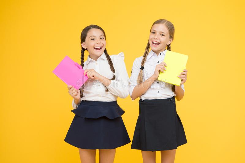 Beyond the Book. little girls in school uniform. cheerful classmates with workbook. dictionary notebook. Get information. Reading story. childrens literature stock images