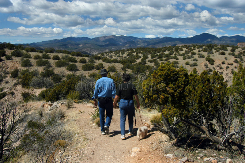 Beyond Retirement. Couple enjoy traveling together. Holding hands and walking with their poodle dog, the two explore Tent Rocks in New Mexico stock photography